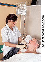 nurse gives a patient an infusion - a nurse gives a patient ...