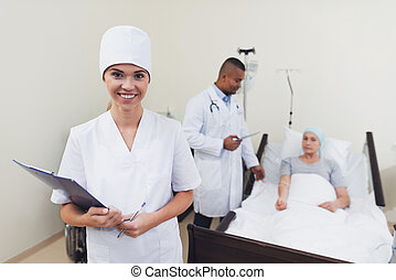 A nurse is posing against the patient's background. She holds a paper tablet in her hands.