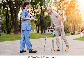 A nurse is standing in the park, next to the old man who goes to her with the help of walkers for adults