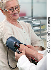 a nurse taking blood pressure of a smiling senior woman
