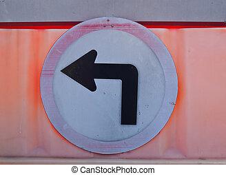 A old turn left road sign on orange barrier