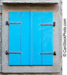 old window with  closed blue wooden shutters