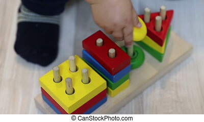 A one year old child puts geometric shapes on pin in wooden ...