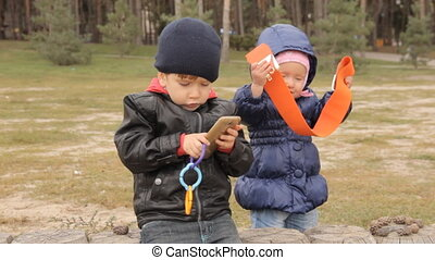 A one year old girl trying on a wide orange belt. A three year old boy pushing buttons in the smartphone sitting next to her on chidlren s wooden fence of short round logs.
