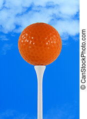 Orange golf ball against blue sky