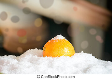 orange in the snow with Christmas decor