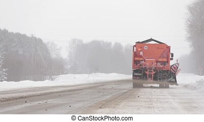 Orange snowplow vehicle featured in winter road sand