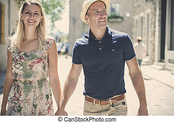 Outdoor lifestyle portrait of young couple in love in old town