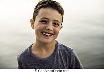 Outdoor portrait of adorable child boy next to lake at the sunset