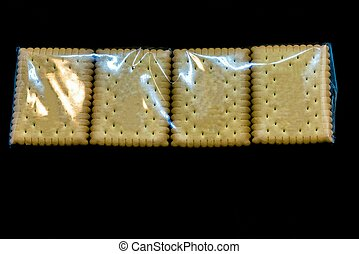 A pack of cookies or crackers in cellophane packaging on a black background. Selective focus