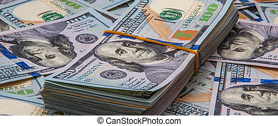 A pack of dollars against the background of scattered bills of a hundred dollars.