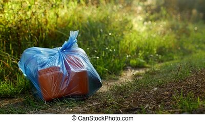 A package of plastic garbage lies in the forest on a forest...