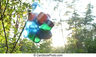 A package of plastic trash hanging in the woods on a tree...