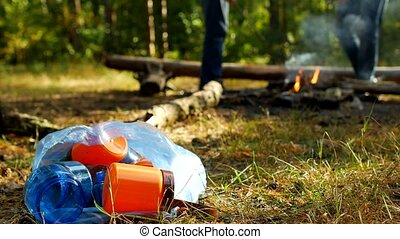 A package with plastic garbage lies on a glade, a fire...