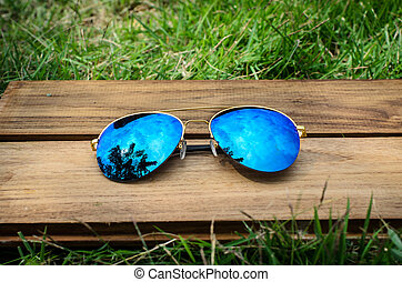 a pair of aviator sunglasses on green grass with blue cloudy sky