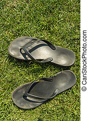 A pair of black rubber flip-flops on the green lawn grass with a copy of the space, summer, outdoor, top view, vertical frame