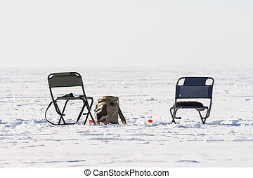 A pair of chairs on the ice during winter fishing.
