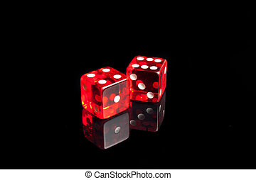 A pair of dice on the black reflecting table