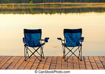 a pair of empty chairs stand on a wooden pier near the lake at dawn