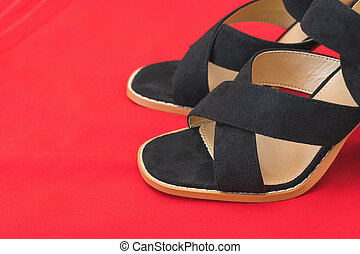 A pair of fashionable women's high-heeled shoes with red fabric.