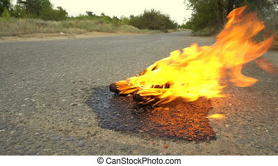 A pair of female shoes in fire on an empty road