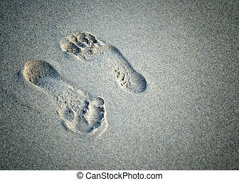 a pair of foot prints left in sand