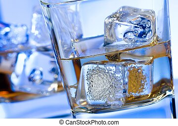 a pair of glasses of alcoholic drink with ice on disco blue light on white table