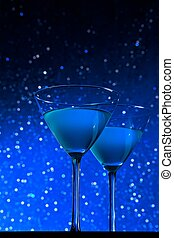 a pair of glasses of blue cocktail on dark blue tint light bokeh background