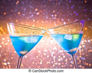 a pair of glasses of fresh blue cocktail with ice make cheers on colorful tint light bokeh with space for text