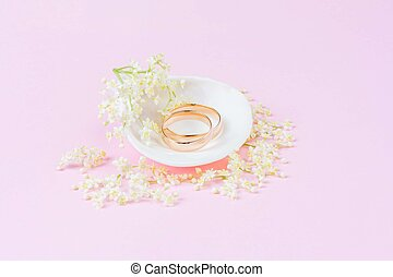 A pair of gold wedding rings in a white seashell with small white flowers on a light pink background