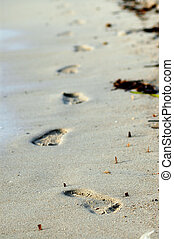 A pair of human footprints in the sand - focus in the front