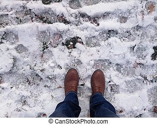 a pair of men's brown boots in the snow