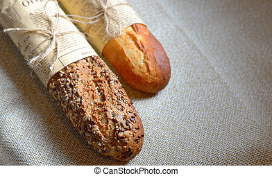 a pair of mini baguette french loaves in newspaper, isolated