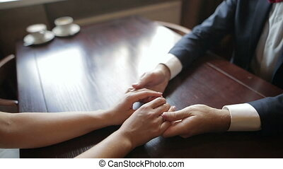 A pair of newlyweds holding hands in a cafe. Close up of human hands.