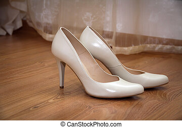 a pair of pale cream-colored wedding women's shoes with...