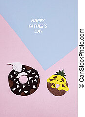 A pair of paper donuts cut out on a colored craft background