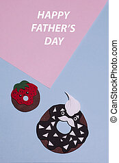 A pair of paper donuts cut out on a colored geometric background