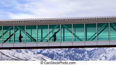A pair of people walking acroos a skywalk between buildings...