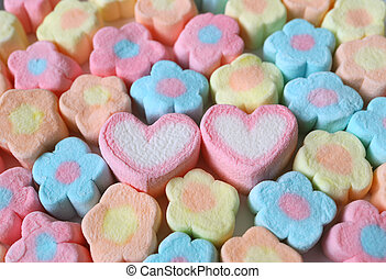 A Pair of Pink and White Heart Shaped Marshmallow Among Lined Up Pastel Flower Shaped Marshmallow Candies