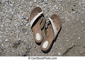 A pair of slippers in the sand by the beach