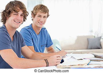 A pair of smiling students as they both look into the camera while they study
