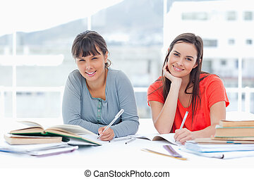 A pair of smiling students studying together as they look at the camera
