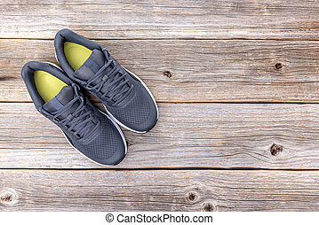 A pair of sneakers on a wooden background.