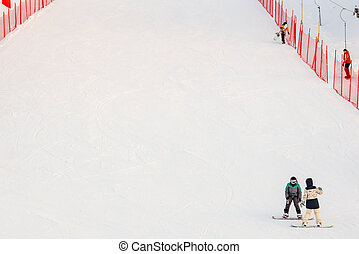 a pair of snowboarders at the end of the track fenced in