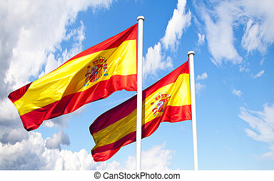 A pair of Spanish Flags waving against a blue sky