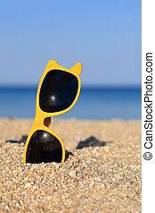 A pair of Sunglasses on the beach