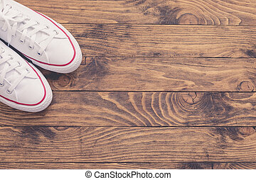 A pair of white canvas shoes or sneakers on a wooden background