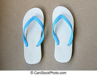 A pair of white slippers beach