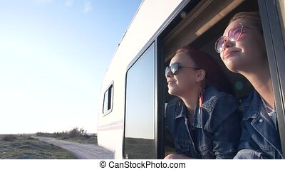 a pair of young women dressed in jeans looks out the window of an autotrailer