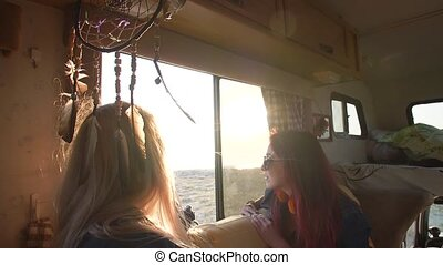 a pair of young women with flying hair in the rays of the sunset on the couch in the autotrailer
